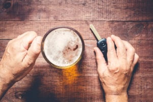 guy holding a car key and about to have a beer